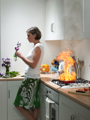 Woman Standing by Kitchen Fire